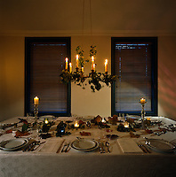 A candelabra draped in ivy hangs above this dining table laid for a candlelit dinner and scattered with autumn leaves