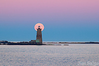 The Harvest Moon rises behind Whaleback Lighthouse in Portsmouth Harbor in New Hampshire