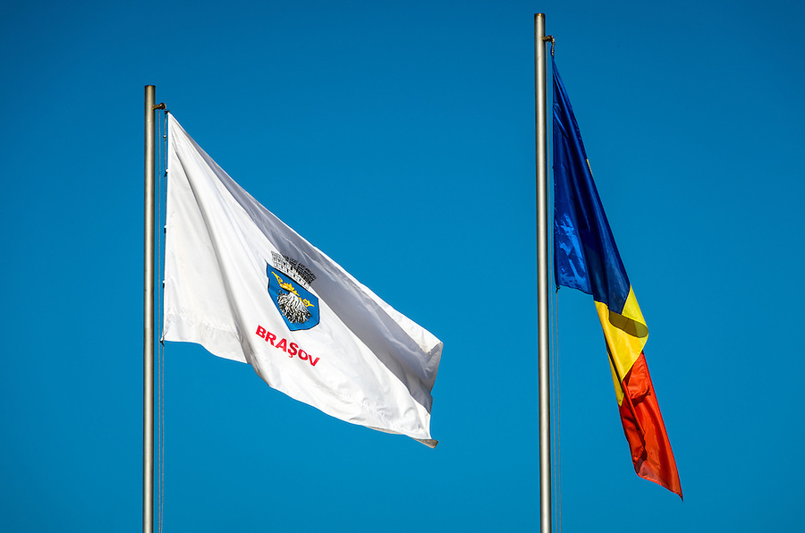 Bra?ov and Romania Flags against a blue sky in the Transylvania region.