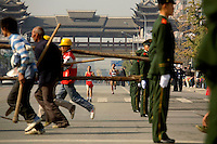 Construction workers push past a police patrol during a marathon race in Beijing, which is getting ready to host the 2008 Olympic Games..