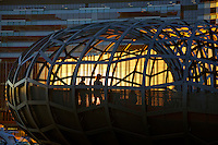 People on lattice walkway bridge at sunset with windows of new ANZ Bank headquarters reflecting sunset behind, Docklands area Melbourne, Victoria. Australia.<br />