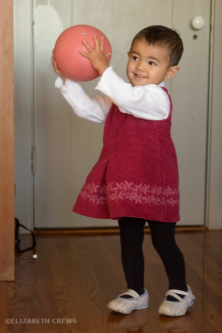 Berkeley CA Nepalese girl, nineteen-months-old joyously playing ball MR