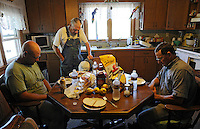 Caption 2<br /> Randell McCloud, center, leads a prayer before lunch with his grandson-in-law Mike Farmer, left, and his son John McCloud on September 25, 2013. The McClouds are active members of their local Baptist church.