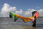 A young man unrolls the kite part of the equipment he will use for kitesurfing off Whale Harbor in the Florida Keys