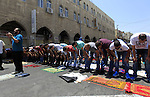 Muslim Palestinians take part in Friday noon prayers in the east Jerusalem neighbourhood of Ras al-Amud on July 31, 2015, following restrictions by Israeli police to allow entry to men only above 50-year-old wanting to access the Al-Aqsa Mosque compound. Photo by Saeb Awad