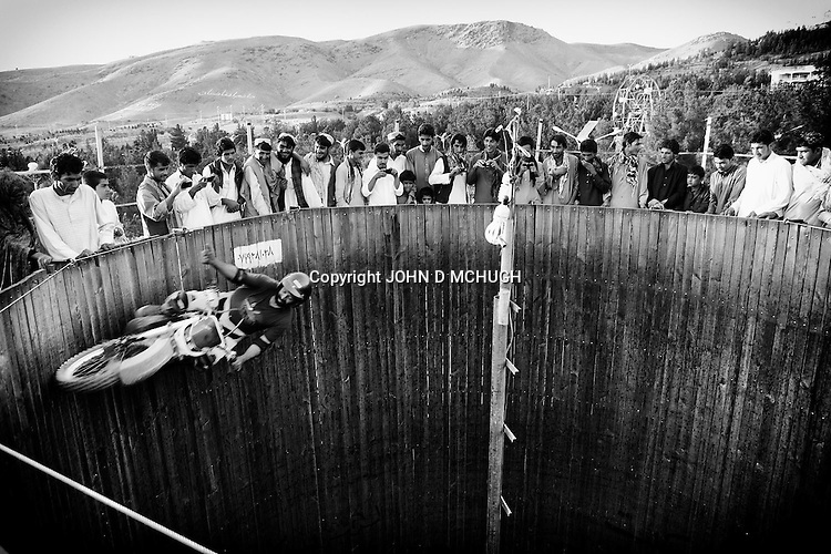 "Afghans watch a motorcycle rider perform in a ""Wall of Death"" in a park in Herat, 20 September 2013. (John D McHugh)"