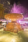 At Bryant Park's ice skating rink, visitors stroll by the colorfully lit fountain in the Winter Village. Manhattan, New York, USA. November 9, 2013.