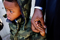 """Gibran Meadows 4, left, holds his father Othello Meadows' hand as they wait in line to see President Obama speak on Wednesday, January 13, 2016, at Baxter Arena in Omaha, Neb. """"I think my son and sons that look just like him are entered into a world that in many cases is very hostile and so him being able to see the highest office in the land manned by someone that looks like him is really powerful,"""" Meadows said."""