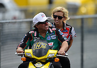 Jun. 17, 2012; Bristol, TN, USA: NHRA funny car driver John Force give his daughter Courtney Force a ride on his scooter during the Thunder Valley Nationals at Bristol Dragway. Mandatory Credit: Mark J. Rebilas-