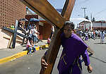 A Nazareno carries a wood cross as he makes his way to the top of Iztapalapa hill where Jesus Christ will be hanged on a cross, April 14, 2006. Almost a million people attend the procession of Good Friday in this  neighborhood of Mexico City, where for o163 years the Iztapalapa neighborhood residents have taken part in a re-enactment of Christ's crucifixion.  Photo by © Javier Rodriguez