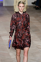 Emily Baker walks the runway in a red camouflage silk long-sleeved button-down safari shirtdress, by Tommy Hilfiger for the Tommy Hilfiger Spring 2012 Pop Prep Collection, during Mercedes-Benz Fashion Week Spring 2012.