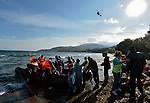 As a Hellenic Coast Guard helicopter stands by, a boat full of refugees disembarks on a beach near Molyvos, on the Greek island of Lesbos, on October 30, 2015. The refugees traveled to Lesbos from Turkey, the boat provided by Turkish traffickers to whom the refugees paid huge sums.