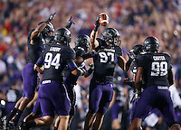 Northwestern defensive players celebrate the recovery of a fumble by Ohio State quarterback Braxton Miller (5) during Saturday's NCAA Division I football game at Ryan Field in Evanston on October 5 2013. (Barbara J. Perenic/The Columbus Dispatch)