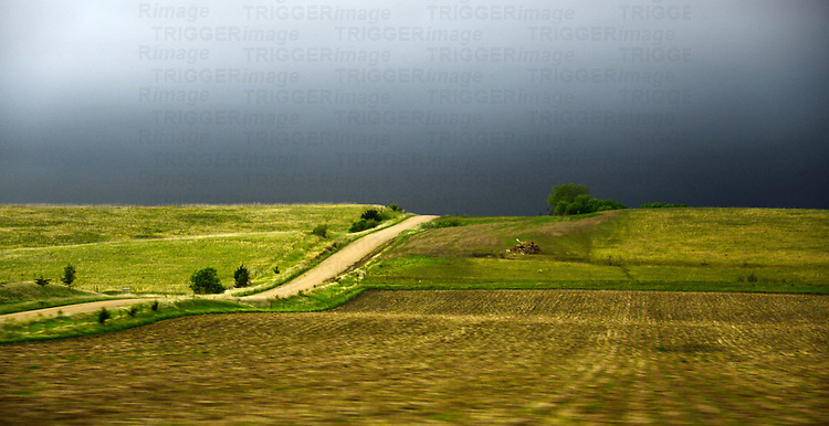 Country scene in USA with rural track disappearing to distance under dark sky
