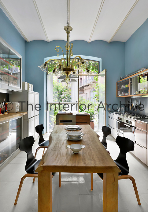 A contemporary blue kitchen with a white tiled floor, barrel ceiling and stainless steel units. A chandelier hangs above a wooden breakfast table and a full height glass door allows access to a garden.