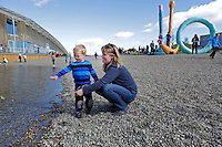 Playing at the new beach outside Astrup Fernley Museum..Aker Brygge is an area in Oslo, Norway. It is a popular meeting place for shopping, dining, and entertainment. As many as 12 million visitors a year make Aker Brygge Norway's biggest destination..Aker Brygge is west of Pipervika, an arm of the Oslo Fjord, on the former ship yard of Akers Mekaniske Verksted, which was shut down in 1982.