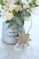 A Christmas decoration propped against a small metal jug containing an arrangement of fresh flowers