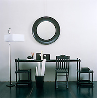Arranged with perfectly elegant sculptural simplicity a black lacquered desk, mirror and standard lamp