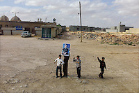 Ben Waled, Libya, March 23, 2011.In this image taken during an organized trip by the Libyan authorities, children display a portrait of the leader at passing foreign journalists.