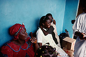 Freetown, Sierra Leone<br /> April 2001<br /> <br /> Jalikaou Tity Turay, 18 (right) and her sister N'yillah Turay (left), 16 are reunited with their mother Yeabu Turay in Freetown, Sierra Leone after 3 years in Guinea as war refugees. Jalikaou Tity Turay is hugged by her brother.