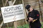 Foto: VidiPhoto<br /> <br /> ARNHEM - Re-enactors oefenen woensdag als Nederlandse en Duitse grenswachters uit de Eerste Wereldoorlog in het Nederlands Openluchtmuseum in Arnhem, terwijl een echtpaar illegaal de grens oversteekt. Het is de opmaat naar de offici&euml;le opening woensdagmiddag van een viertal bijzondere exposities, onderdeel van de toekomstige Canon van Nederland die in 2017 klaar moet zijn. Een van de meest bijzondere verbeeldingen is een nagebootste grens uit de Eerste Wereldoorlog tussen Nederland en Belgi&euml; met wachtposten, prikkel- en stroomdraad. Smokkelaars en vluchtelingen probeerden in die tijd met behulp van technieken, zoals een passeursraam die de stroomdraden uit elkaar moest houden, illegaal de grens te passeren. Door het hoge voltage was dat vaak met dodelijke afloop. Bezoekers mogen het passeursraam zelf uitproberen tijdens een smokkelspel. Om de werkelijkheid zo veel mogelijk te benaderen, staan de grensdraden onder spanning van (slechts) 12 volt. Het Nederlands Openluchtmuseum is door de overheid aangewezen om in 2017 de offici&euml;le Canon van Nederland te presenteren. De Canon bestaat uit vijftig belangrijke personen, creaties en gebeurtenissen die laten zien hoe Nederland geworden is tot het land waarin we nu leven. Foto: Een Nederlandse wachtpost knijpt een oogje toe.