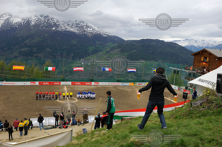 A supporter gingerly coming down a slipperly slope carrying beer at the other official Euro 2008 football tournament: the European Championship of Mountain Villages. The tournament was held at the summer training ground of hosts FC Gspon, standing at 2008 metres above sea-level,  and surrounded by 4000 metre alpine peaks. It is the highest football pitch in Europe, and reachable only by cable car, or a long walk. Amateur league teams from eight countries took part.