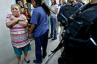 A frightened women weeps during a drug sweep by Tijuana Police officers in Colonia Chula Vista  in Tijuana, Mexico.