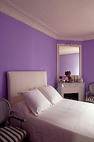 Clutter has been kept to a minimum in the bedroom where the walls are painted a bright yet calming shade of purple