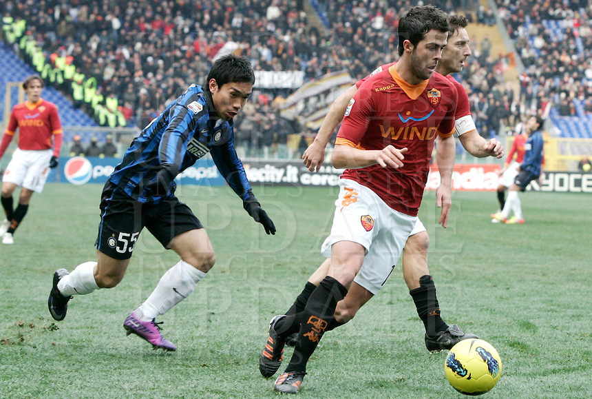 Calcio, Serie A: Roma-Inter. Roma, stadio Olimpico, 5 febbraio 2012..Football, Italian serie A:. AS Roma vs Inter Milan. Rome, Olympic stadium, 5 february 2012..AS Roma midfielder Miralem Pjanic, of Bosnia, right foreground, flanked by teammate Francesco Totti, is chased by Inter Milan defender Yuto Nagatomo, of Japan, left..UPDATE IMAGES PRESS/Riccardo De Luca