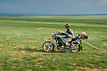 Mongolian horsemen in traditional costume carying his hearding pole on his motorbike in the grasslands of Inner Mongolia, China.