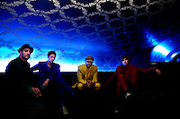 """Los Angeles, California, November 27, 2010 - A portrait of the band Ok Go, from left, drummer, Dan Konopka (green), lead singer/guitarist, Damian Kulash (blue), bass guitarist/singer, Tim Nordwind (yellow), and guitarist/singer, Andy Ross (red), in the VIP lounge at the Nokia Club. OK Go was wrapping up a 16-month world tour by playing a song for Yo Gabba Gabba! during the day and later a final show at the Nokia Club. The Grammy Award-winning band has earned considerable fame for their creative, often low-budget music videos that are released on YouTube. Many have gone viral, including the 2006 video for """"Here It Goes Again"""", where the band performs a complex routine on treadmills. It has received over 50 million views to date. Kulash says the band left their major label and began their own to assert more creative control over their music and their videos. Adding, """"We're among the first musicians to view our YouTube videos as standalone artistic output, not advertisement for our recordings, and it shows in the numbers: over the past decade, we've sold a little over 600,000 records globally, and our videos have combined views in excess of 125 million.""""."""