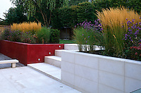 A red Venetian plaster and white limestone wall forms a terrace to the garden with steps leading to the back garden