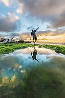 A man balances himself as he walks near a kelp-lined pond along a rocky seashore at sunset, Pua'ena Point, North Shore, O'ahu.