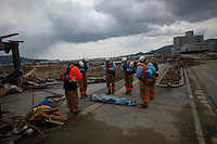 Rescue workers pay respect next to the body they retrieved from the rubbles in Rikuzentakat days after the area was devastated by a magnitude 9.0 earthquake and tsunami March 17, 2011.   REUTERS/Damir Sagolj (JAPAN)
