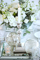 A table arrangement of stocks and roses behind a silver candlestick and glass baubles
