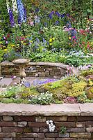 Colorful mixed perennial flower garden with Delphinium, sempervivum rock garden, bird bath, and climbing plants, circular sunken patio, raised beds, Laburnum tree, blue,yellow, red, pink colors