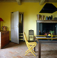 In the kitchen an interesting mix of antique and contemporary furniture can be found againt a backdrop of walls painted in vivid yellow pigment