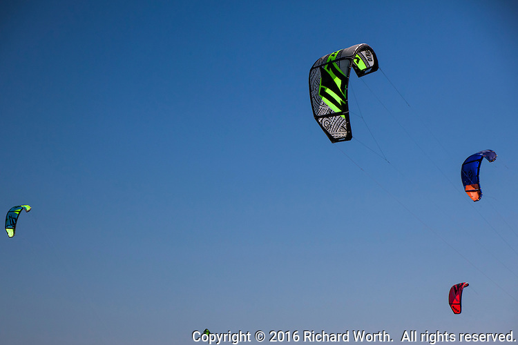 Five brightly colored kiteboard kites float against a clear blue sky over San Francisco Bay.