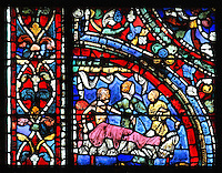 The younger son, naked, is put to bed by a servant, while a woman holds him around the neck, from the Parable of the Prodigal Son stained glass window, in the north transept of Chartres Cathedral, Eure-et-Loir, France. This window follows the parable as told by St Luke in his gospel. It is thought to have been donated by courtesans, who feature in 11 of the 30 sections. Chartres cathedral was built 1194-1250 and is a fine example of Gothic architecture. Most of its windows date from 1205-40 although a few earlier 12th century examples are also intact. It was declared a UNESCO World Heritage Site in 1979. Picture by Manuel Cohen