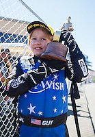 Jul 30, 2016; Sonoma, CA, USA; Guy Brizzee celebrates with a trophy after having his Make-A-Wish dream come true to be an NHRA race car driver during qualifying for the Sonoma Nationals at Sonoma Raceway. Brizzee is battling leukemia. Mandatory Credit: Mark J. Rebilas-USA TODAY Sports