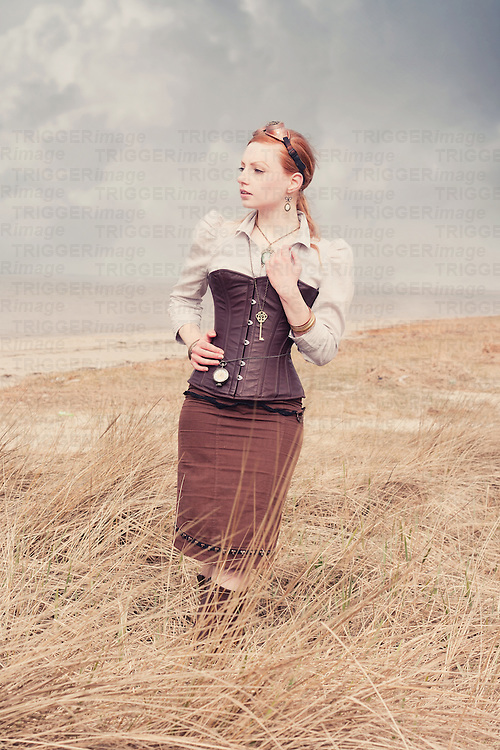 Young woman with red hair wearing goggles and corset standing alone outdoors beside the sea