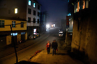 People walk through the streets of Xinjie at night in Yuanyang County, Yunnan Province, China.