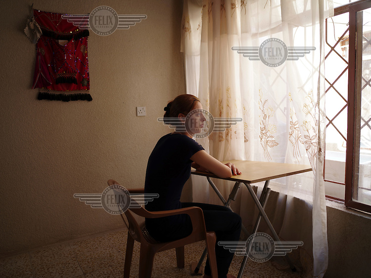 Nazlin, 24, from Zoraba village in Sinjar, sitting in a house in the Sharia district near Dohuk where she fled with her family. 'When I was living in Sinjar, I often visited Yazidi temples in the Sinjar mountains, but most of these temples were destroyed by ISIS.'