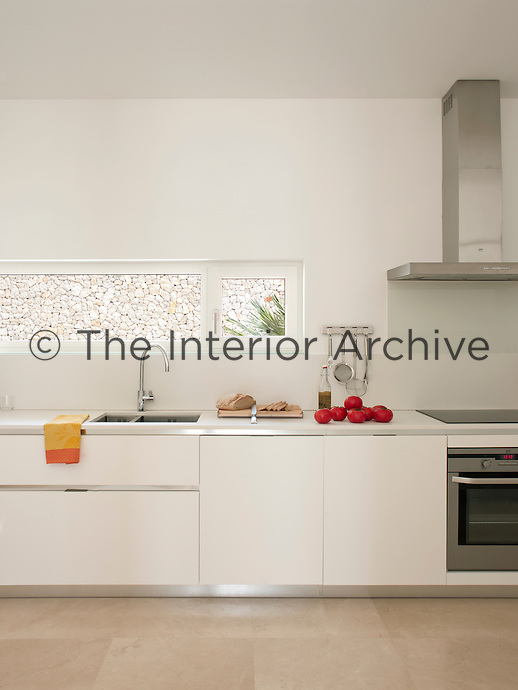 A modern, white kitchen with a sand-blasted stone floor. A stainless steel extractor fan is set above a ceramic hob and integral oven. A sink is set beneath a narrow window.