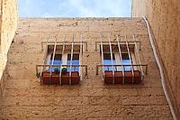 Two barred windows with planters in the stone wall of a house in the Jewish Quarter of the Old City of Jerusalem.