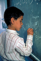 LITTLE BOY WRITING ON BLACKBOARD. CHILD IN SCHOOL. BASRAH, IRAQ SOUTHERN IRAQ.
