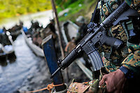 A Panamanian soldier, carrying an automatic rifle, embarks on a canoe while escorting immigrants in the jungle of Darién gap in Panama, 27 January 2015.