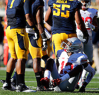 Ohio State Buckeyes quarterback Kenny Guiton (13) looks up at California Golden Bears linebacker Nick Forbes (1) after a bad snap went over his head in the 1st quarter at Memorial Stadium in Berkeley, California on September 14, 2013.  (Dispatch photo by Kyle Robertson)