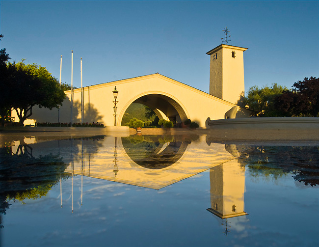 Puddle from overnight rain reflects front of Robert Mondavi winery