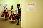 Dancers of the Bolshoi ballet warmed up next to the stage during a performance of Massine's Le Tricorne at the Bolshoi Theatre's New Stage in Moscow.  On the wall was a notice asking for quiet during the performance. Moscow, Russia, January 25, 2007